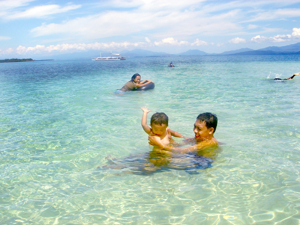 Photo of family swims clear blue ocean at Palawan Philippines Puerto Beach Resort