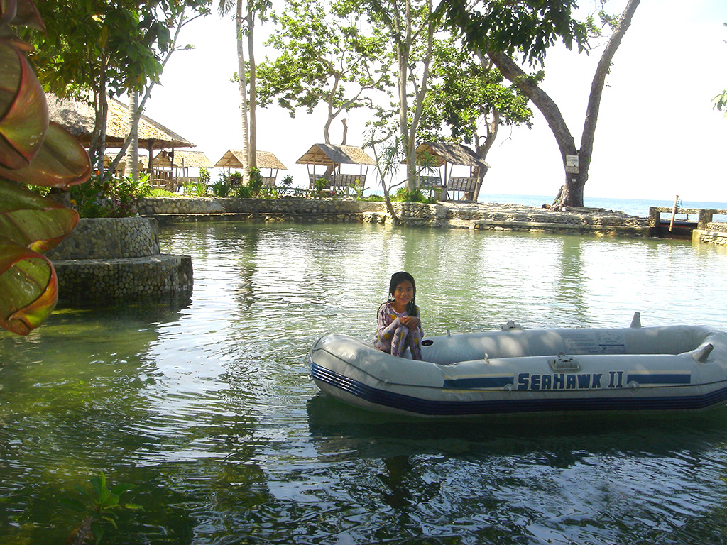 Photo of young girl sitting in an inflatable boat in shaded freshwater lagoon ringed by seaside palapas at Palawan Philippines Puerto Beach Resort