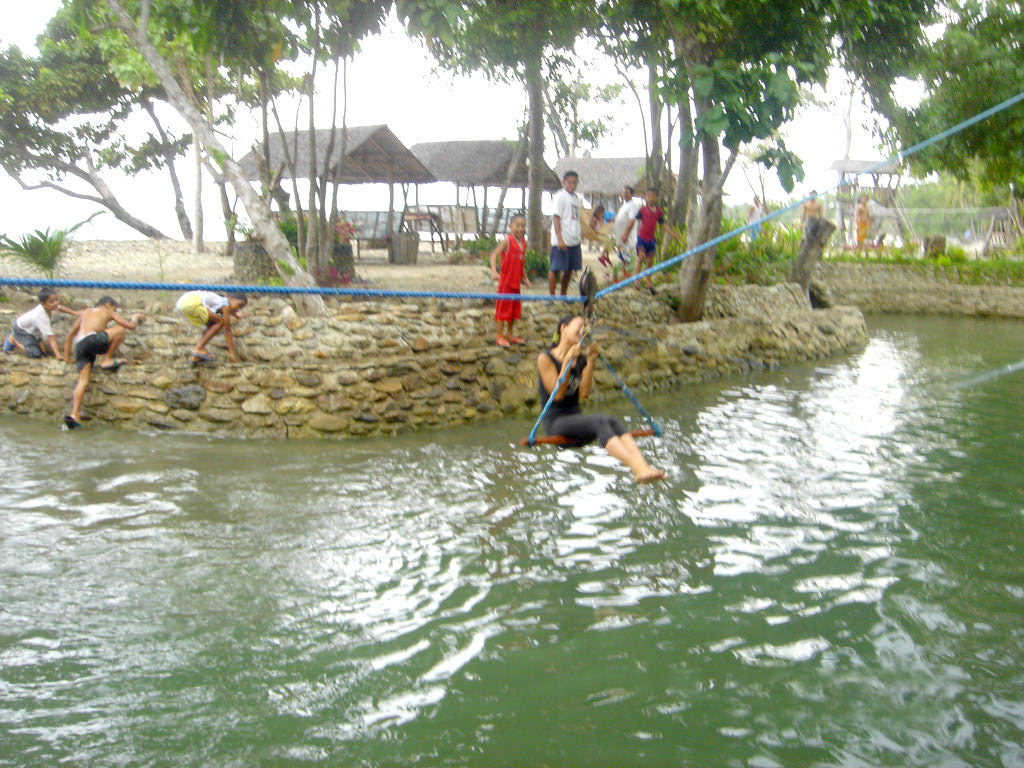 Photo of girl laughing as she rides zipline skimming surface of freshwater lagoon as several children watch or run around beside water's edge at Puerto Beach Resort
