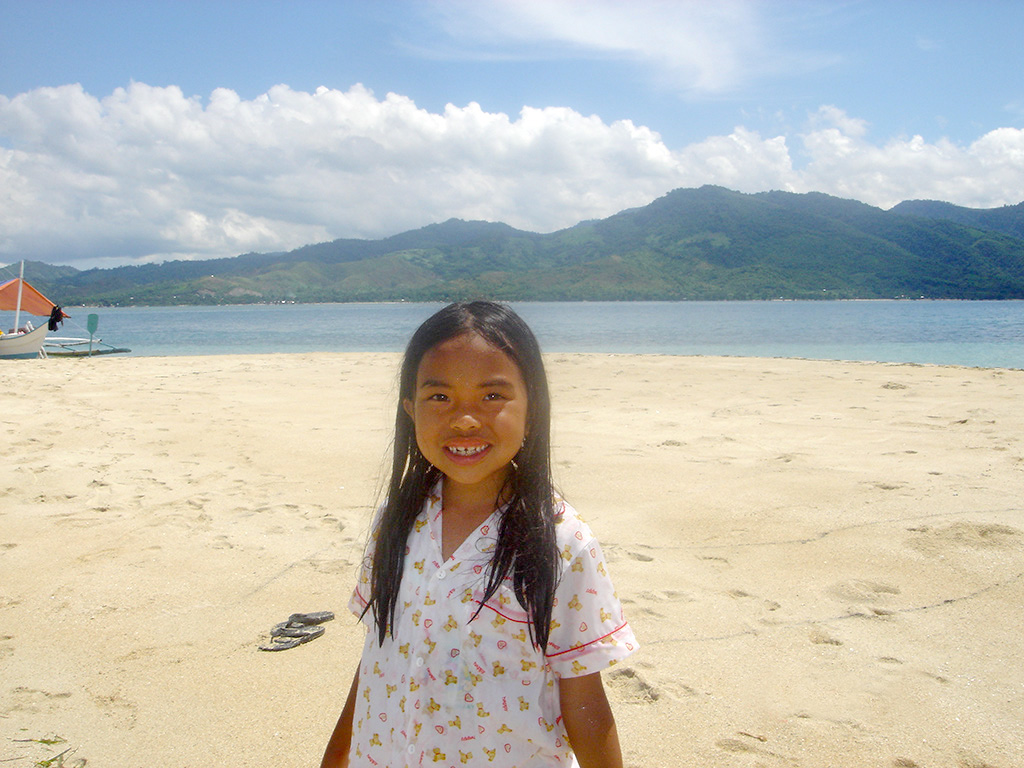 Photo of young girl smiling on sandy beach Palawan Philippines Puerto Beach Resort