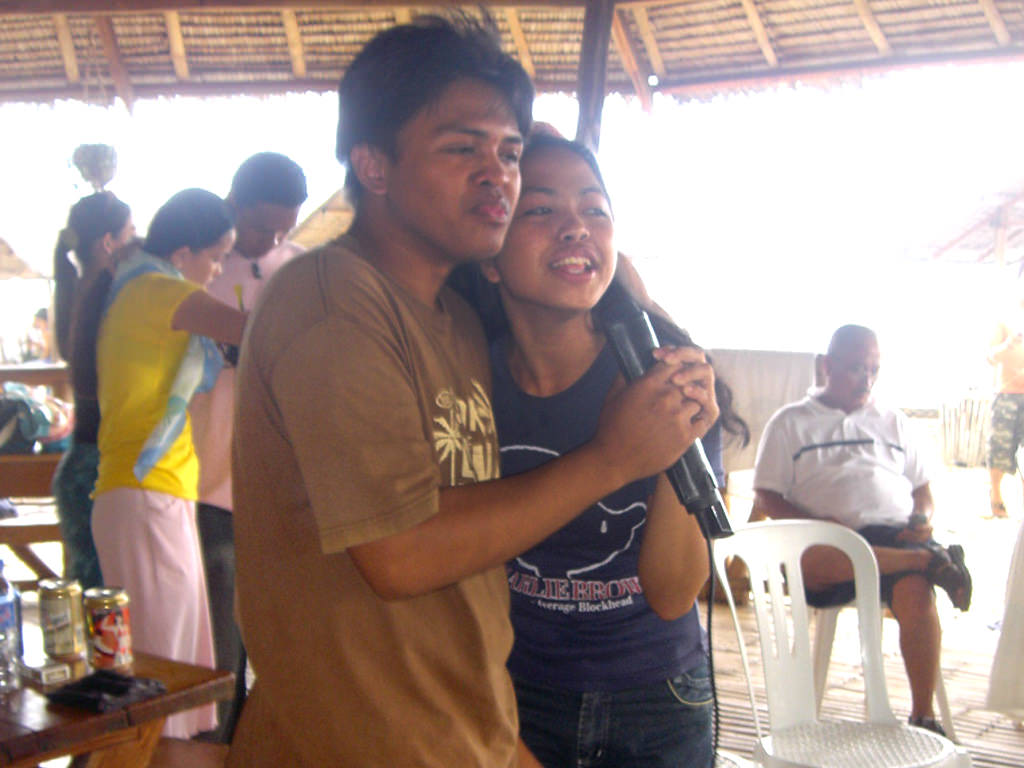 Photo of young couple sharing a mic to sing in pavilion at Puerto Beach Resort