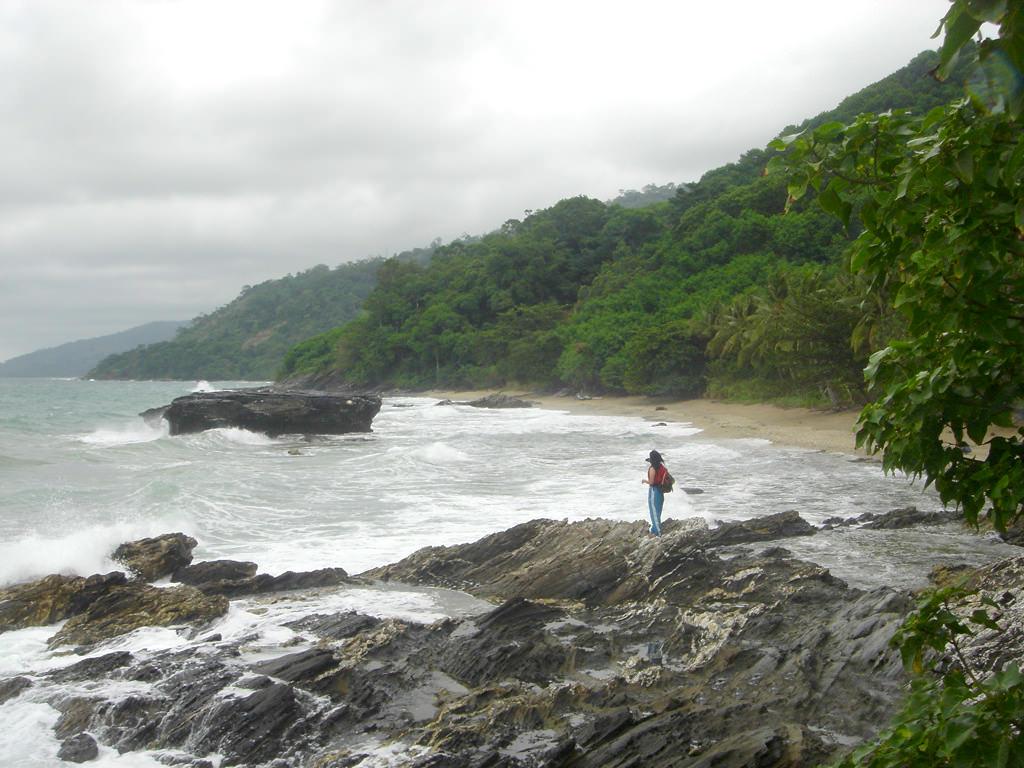 Photo of woman standing on rugged rocky coast of Honda Bay, Palawan, Philippines, near Puerto Beach Resort