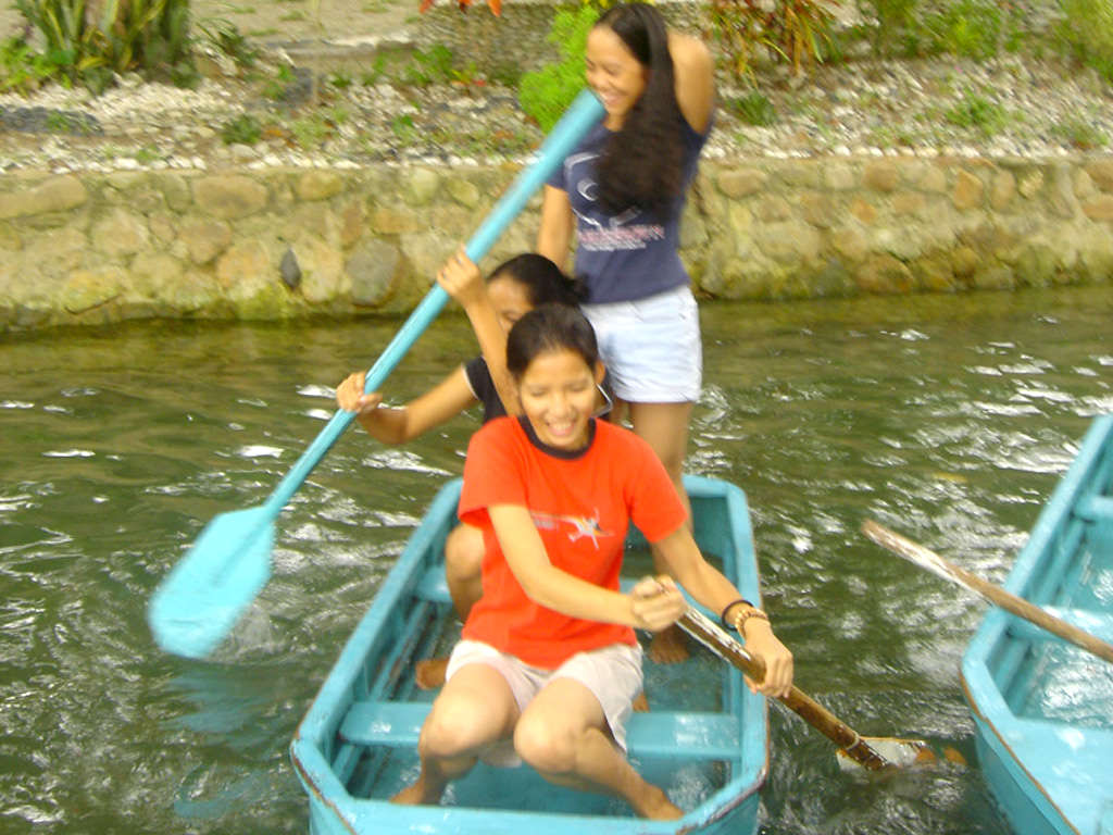 Photo of three girls in a blue wooden boat laughing, one standing, two with paddles, in the Puerto Beach Resort freshwater seasonal lagoon.
