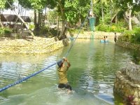 Photo of lagoon as boy rides zipline into water while others paddle a blue wooden boat at Puerto Beach Resort