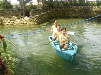 Photo of three girls with paddles piloting a small blue wooden boat in freshwater lagoon at  Puerto Beach Resort.