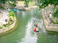 Photo of freshwater lagoon with two young boys clinging to bar attached to zipline as they ride down to splash into water, go swmming at Puerto Beach Resort.