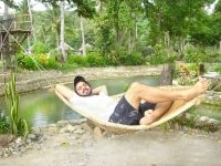 Photo of man smiling as he sleeps in a hammock beside freshwater seasonal lagoon of Puerto Beach Resort.
