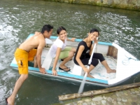 Photo of three swimmers climbing into a blue wooden boat ready to push off with paddles into freshwater lagoon at Puerto Beach Resort