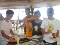 Four young people in t-shirts serve themselves pasta in Puerto Beach Resort Cafe and Grill.