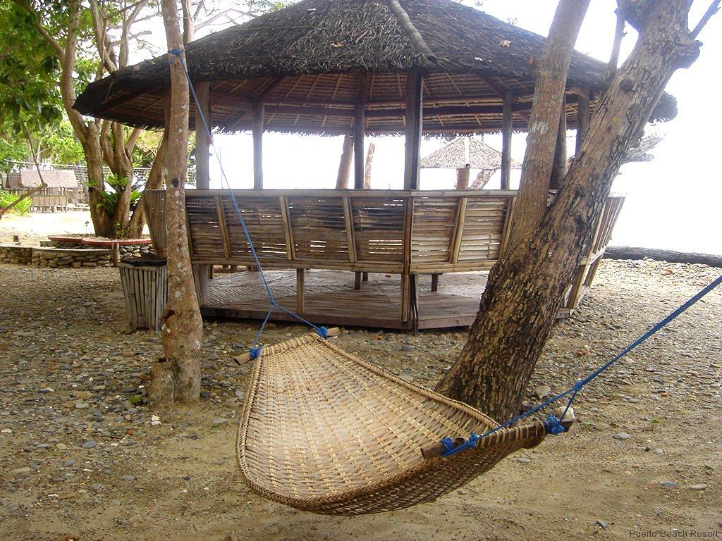 Photo of hammock and medium sized palapa with ocean behind at Puerto Beach Resort