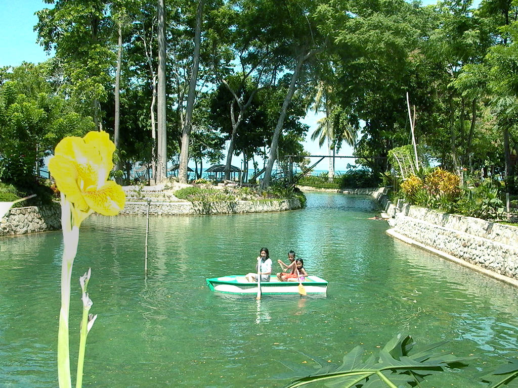 Photo of three kids paddling blue wooden boat in freshwater river-fed lagoon with bright yellow flower foreground, bright blue ocean visible beyond row of trees and palapas at Puerto Beach Resort