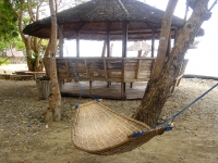 Photo of hammock and medium sized palapa with ocean behind at Puerto Beach Resort