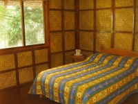 Photo of queen-size bed, natural fiber wall coverings in a cottage at Puerto Beach Resort