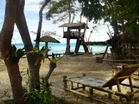 Photo of seaside treehouse and palapas on the beach with a chaise lounge at Palawan Philippines Puerto Beach Resort