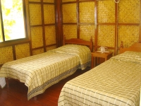 Photo of two twin-size beds in air-conditioned cottage bedroom at Puerto Beach Resort